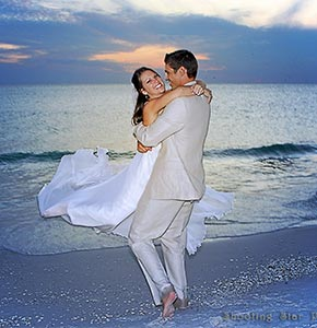 Bride smiling in arms of groom by gulf water at dusk