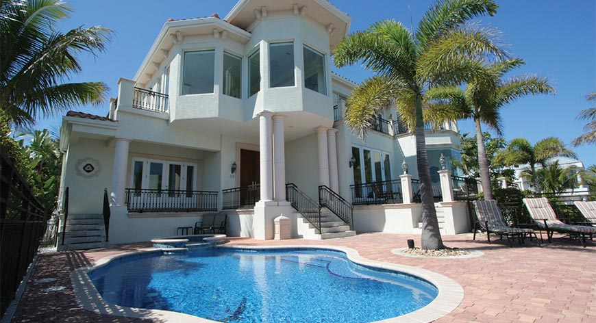 Home with columns and pool and palm trees