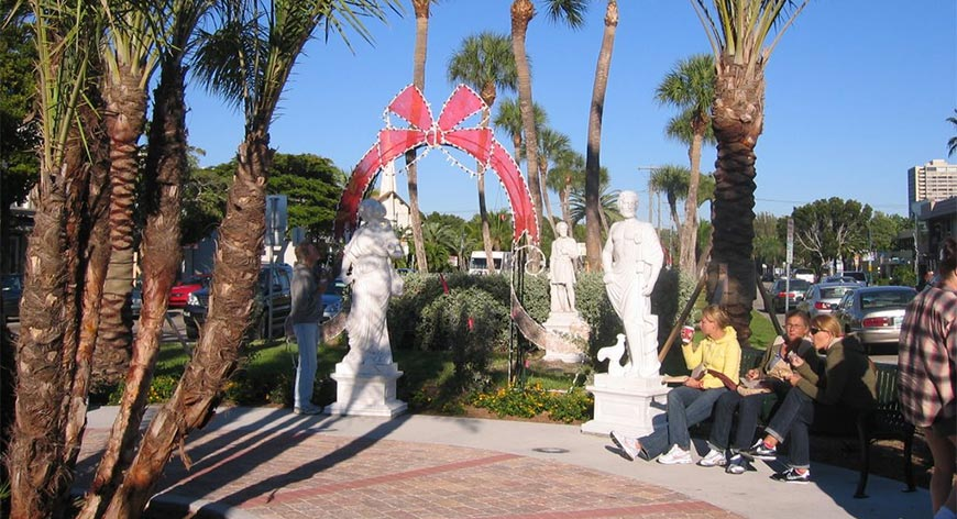 People relaxing in center of circle with statues